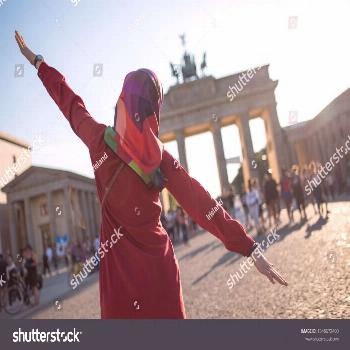 Muslim woman in front of the Brandenburg gate in Germany with open arms happy in Berlin on a sunny